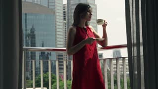 Young woman drinking coffee on the terrace in the city