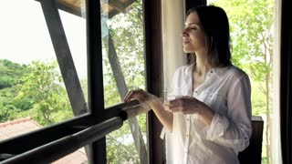 Young  woman drinking water and enjoying beautiful view from the window