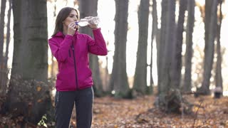 Young woman drinking water man jogging in the forest super slow motion, shot at 240fps