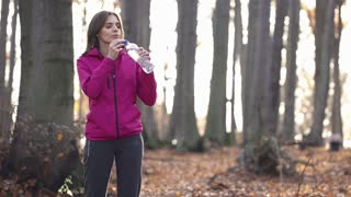 Young woman drinking water man jogging in the forest