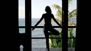 Young woman exercising, doing yoga pose on terrace with sea view, 4K