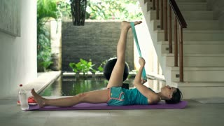 Young woman exercising legs with band in luxury villa, 4K