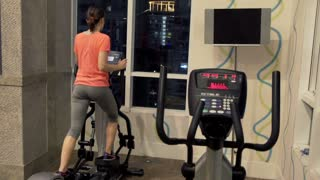Young woman exercising on elliptical machine in the gym