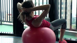 Young woman exercising on fit ball in gym, super slow motion 120fps