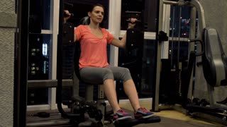 Young woman exercising with body building equipment in the gym