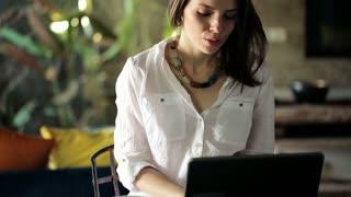 young woman finish work on laptop, drinking tea and relaxing at home