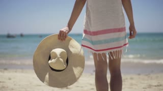 Young woman holding hat on beautiful exotic beach slow motion 240fps