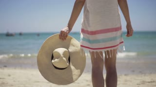 Young woman holding hat on beautiful exotic beach