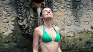 Young woman in bikini taking bath in hot springs in bali super slow motion, 240Fps