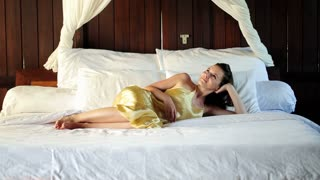Young woman in nightgown relaxing on comfortable bed