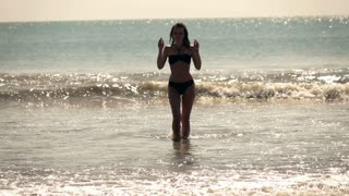 Young woman in swimsuit walking on the sea, super slow motion
