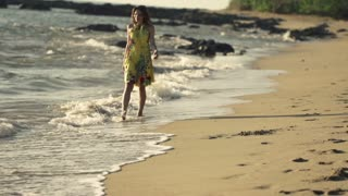 Young woman in yellow dress walking on the beach, 240fps