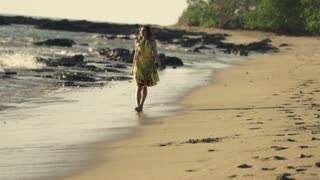 Young woman in yellow dress walking on the beach
