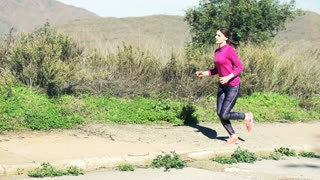Young woman jogging, man doing laces on the trunk in the mountains, super slow motion 240fps