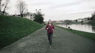 Young woman jogging on path by city river, super slow motion, shot at 240fps