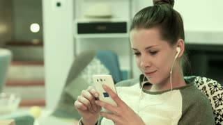 Young woman listening to music on cellphone sitting on chair at home