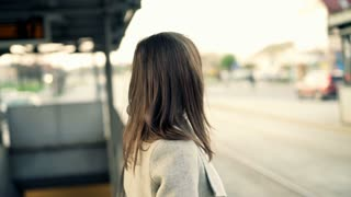 Young woman looking around and waiting for a bus at bus stop