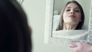 Young woman looking in the mirror her makeup lips at beauty salon