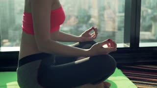 Young woman meditating on mat by the window with city view