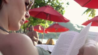 Young woman on sunbed reading book on the beach, 4K