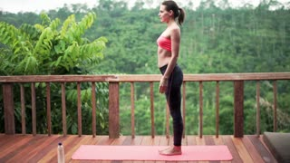 Young woman on terrace with tropical view exercising yoga, doing warrior pose
