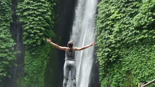 Young woman open arms to amazing waterfall in Bali super slow motion, 240Fps