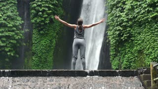 Young woman open arms to amazing waterfall in Bali