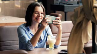 Young woman playing game on smartphone sitting  in the cafe