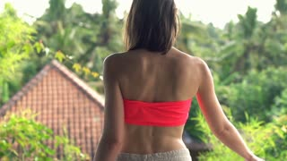 Young woman putting on shirt while standing in terrace with beautiful garden view