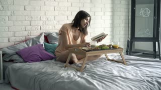 Young woman reading book, eating and drinking coffee sitting on bed, 4K