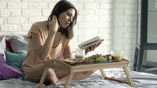 Young woman reading book, eating and drinking coffee sitting on bed