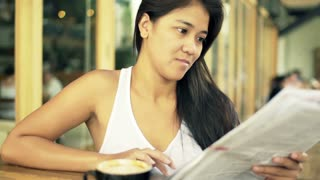 Young woman reading newspaper, drinking coffee in cafe