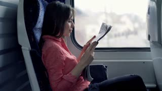 Young woman reading newspaper while sitting on the train