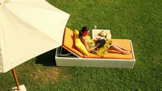 young woman relaxing with laptop on sunbed