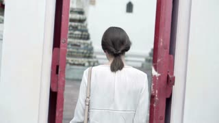 Young woman sightseeing and taking photo of Buddhist temple with cellphone in Thailand