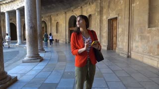 Young woman sightseeing with smartphone old amphitheatre building, super slow motion