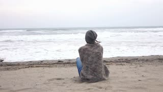 Young woman sitting on the autumn beach and looking on the sea, 240fps