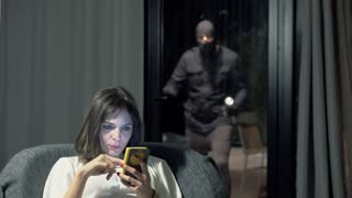 Young woman sitting with smartphone in her home when man in balaclava attack her