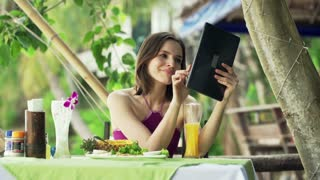 Young woman sitting with tablet in outdoor restaurant with exotic garden in Thailand