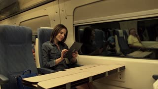 Young woman sitting with tablet in the night train