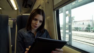 Young woman sitting with tablet in the train