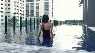 Young  woman splashing legs on edge of swimming pool, slow motion