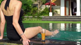 Young woman splashing legs on the swimming pool edge super slow motion 240fp