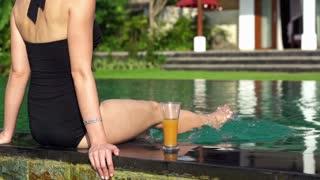Young woman splashing legs on the swimming pool edge