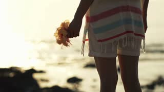 Young woman standing with flower close to the sea during sunset, shot at 240fps