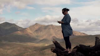 Young woman standing with smartphone on the country with splendid mountains view