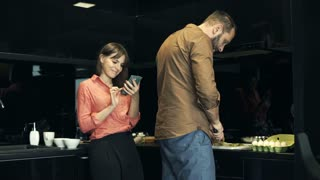 Young woman standing with smartphone while her husband preparing breakfast in the kitchen