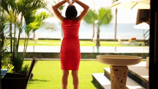 young woman stretching arms enjoying luxury view at sea and swimming pool