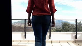Young woman stretching arms while standing on terrace with mountains view, 4K