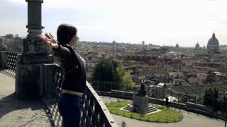 Young woman stretching her arms on terrace with splendid Rome view, super slow motion